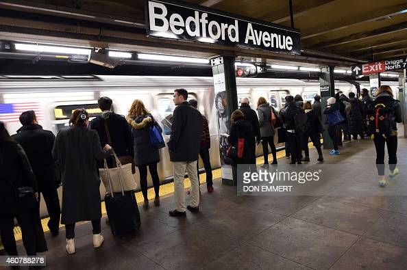 Commuters at the Bedford Ave subway station wait as the train arrives December 22 2014 in New York The last stop that the L train makes before...