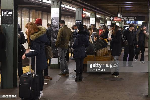 Commuters at the Bedford Ave subway station wait for a train December 22 2014 in New York The last stop that the L train makes before traveling to...