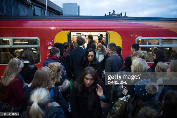 Commuters attempt to board a full Southwest Train carriage toward central London as others alite at Clapham Junction station in London on January 10...