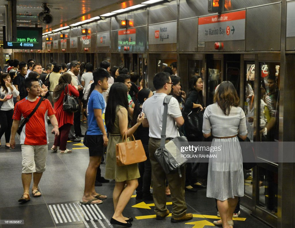 Commuters boarding a crowded train at the subway station in Singapore on February 13, 2013. Singapore on February 4 defended its population policies after an outcry over a forecast that it could have 30 percent more people in less than 20 years, with foreigners forming almost half the total.