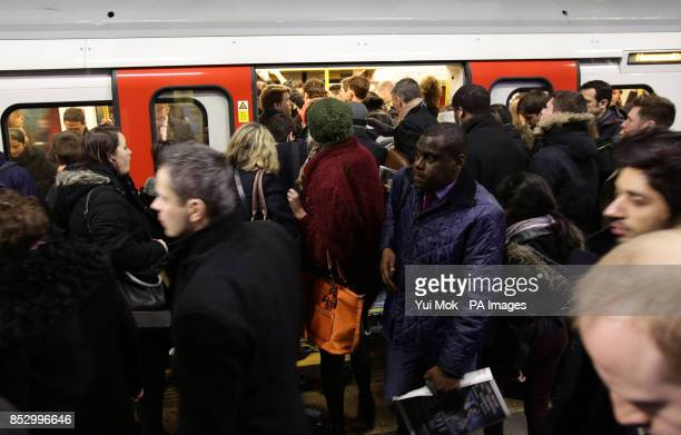 Commuters boarding a train at Farringdon Underground station London during a 48hour tube strike as London Underground workers strike over planned job...
