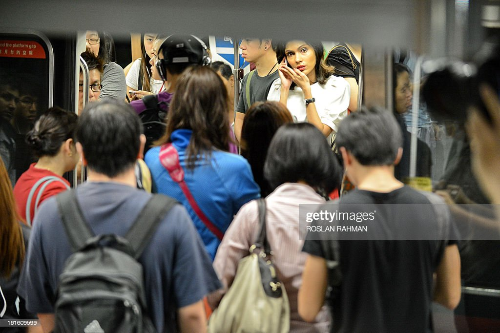 Commuters boarding the train at the subway station in Singapore on February 13, 2013. Singapore on February 4 defended its population policies after an outcry over a forecast that it could have 30 percent more people in less than 20 years, with foreigners forming almost half the total. AFP PHOTO / ROSLAN RAHMAN