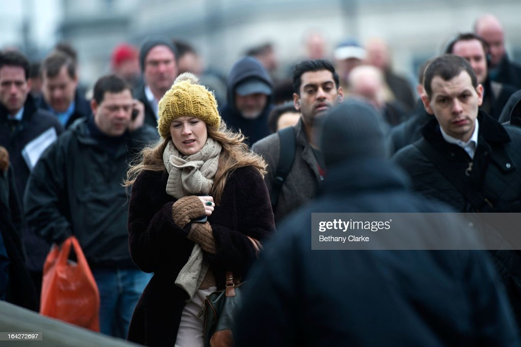 Commuters brave the cold weather as they walk across London Bridge on March 22, 2013 in London, United Kingdom. The UK is facing a day of severe weather disruption, with flood and snow warnings issued in a number of regions across the country. Forcasters have said to expect freezing temperatures and snow in London over the weekend.