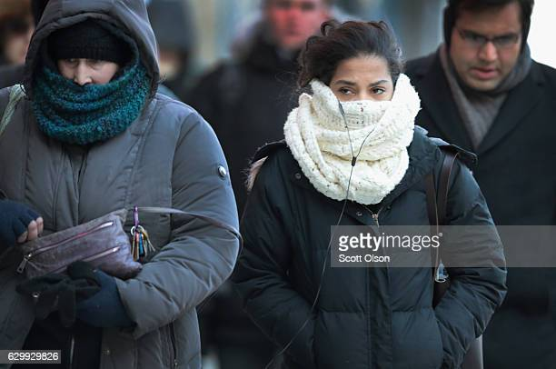 Commuters bundled for warmth walk toward an L station on December 15 2016 in Chicago Illinois The Chicago area is experiencing the season's first...