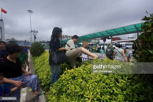 Commuters climb over bushes and railings in the middle of a main road after underground passageways were blocked by floodwaters brought on by Typhoon...