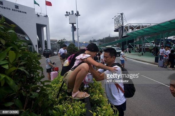 Commuters climb over bushes and railings in the middle of a main road due to underground passageways being blocked by floodwaters caused by Typhoon...