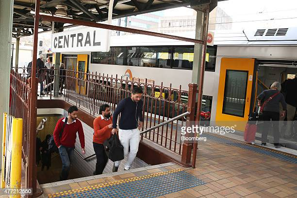 Commuters climb up a flight of stairs as passengers board a train at Central Station in Sydney Australia on Tuesday June 9 2015 Australian wages fell...