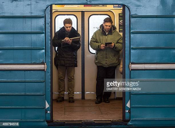 Commuters consult their electronic connected devices inside a train coach in the Moscow Metro on December 1 2014 the Moscow Metro now has its...
