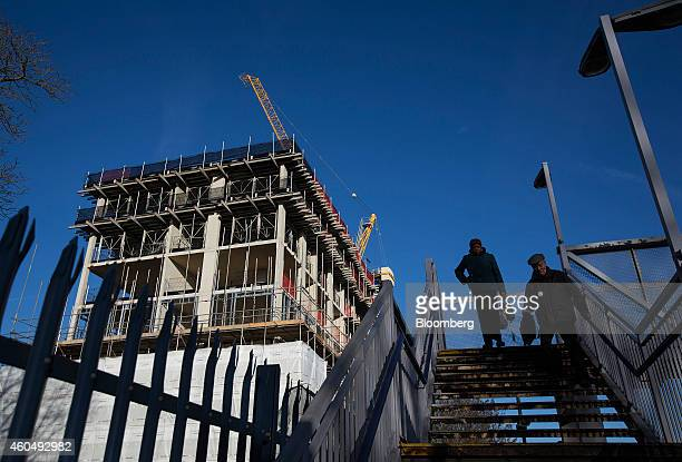Commuters cross a footbridge near the 'Catford Green' residential apartment complex as it stands during construction by Barratt Developments Plc in...