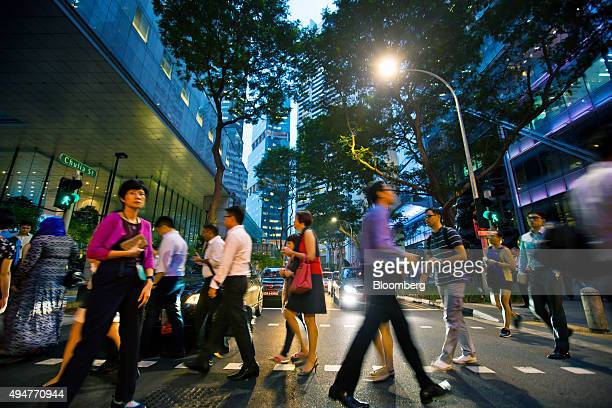 Commuters cross a road at dusk in the central business district of Singapore on Wednesday Oct 28 2015 Singapore's third quarter unemployment rates...