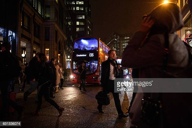 Commuters cross a road in the rain in front of a bus outside Liverpool Street Station on January 9 2017 in London England Millions of people are...