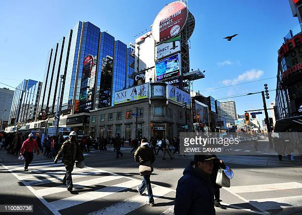 Commuters cross a street in downtown Toronto Ontario on March 14 2011 The number of jobs in Canada rose for the third consecutive month in February...