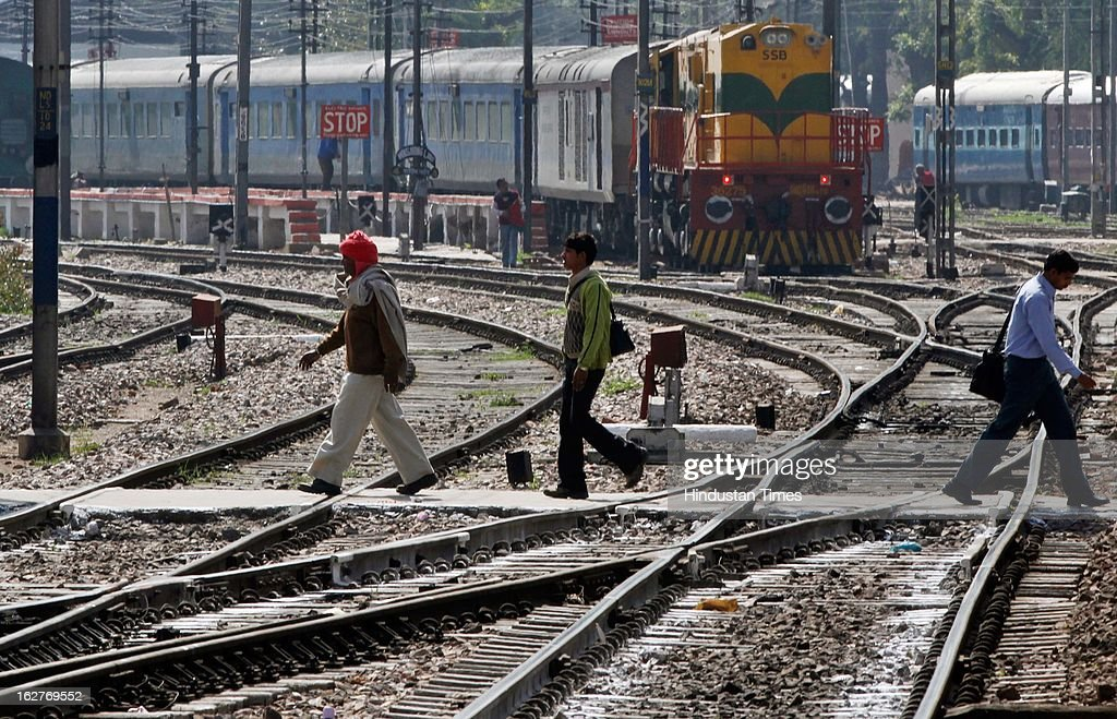 Commuters cross the railway tracks as train is coming at New Delhi Railway Station on February 26, 2013 in New Delhi, India. Indian Railway Minister Pawan Kumar Bansal presented his maiden Railway budget for the next fiscal year in the parliament.