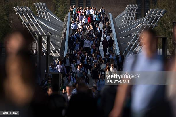 Commuters cross the river Thames using the Millennium footbridge during a tube strike in London on July 9 2015 London's roads buses and overland...
