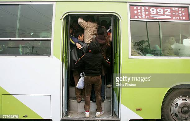 Commuters crowd a bus in the morning rush hour at a bus station on November 7 2007 in Beijing China Beijing has five rail lines totaling 708 miles...