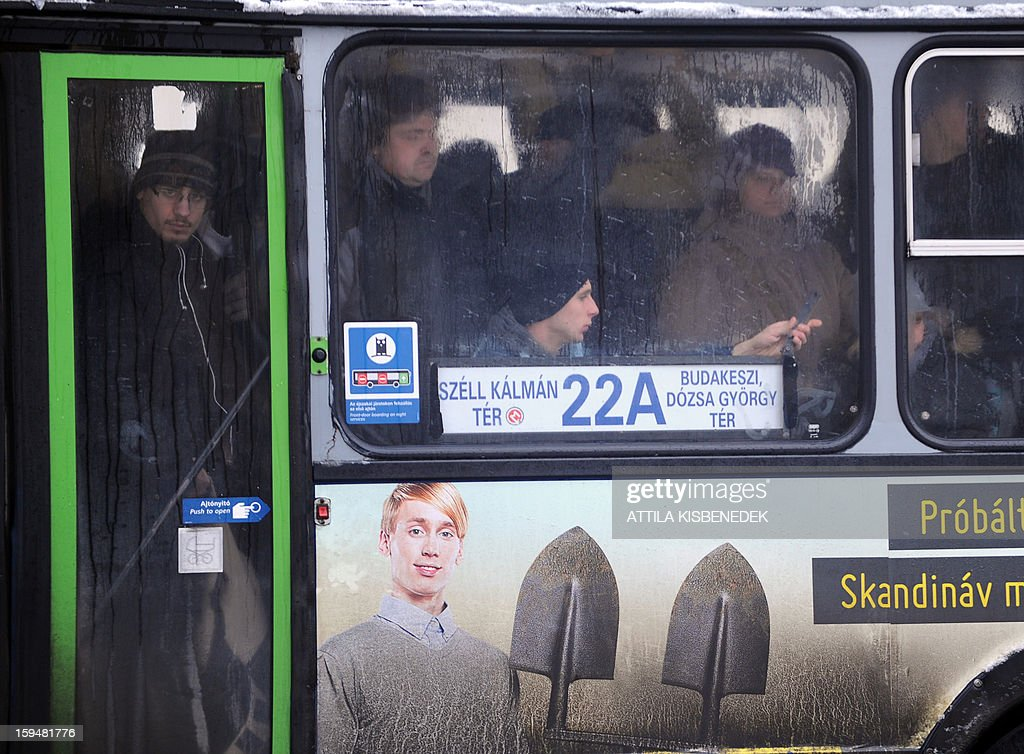 Commuters crowd in a bus in Budapest, 12th district on January 14, 2013 as the Hungarian capital and several counties were hit by about 20 cm snow last night and this morning. The heavy snowfalls caused chaos in traffic and public transport. AFP PHOTO / ATTILA KISBENEDEK