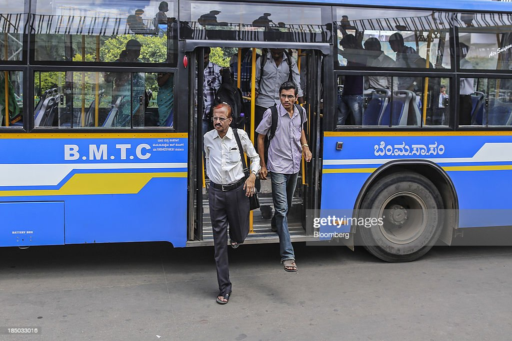 Commuters disembark a bus at a station in Bangalore, India, on Saturday, Oct. 12, 2013. Reserve Bank of India Governor Raghuram Rajan has turned the rupee from a pariah to the worlds favorite currency after just a month in office as he intensifies efforts to quell inflation and lure capital. Photographer: Dhiraj Singh/Bloomberg via Getty Images