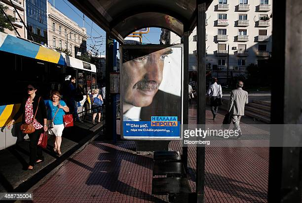 Commuters disembark a bus by a preelection poster depicting Evangelos Meimarakis the leader of the New Democracy Party of Greece in Athens Greece on...