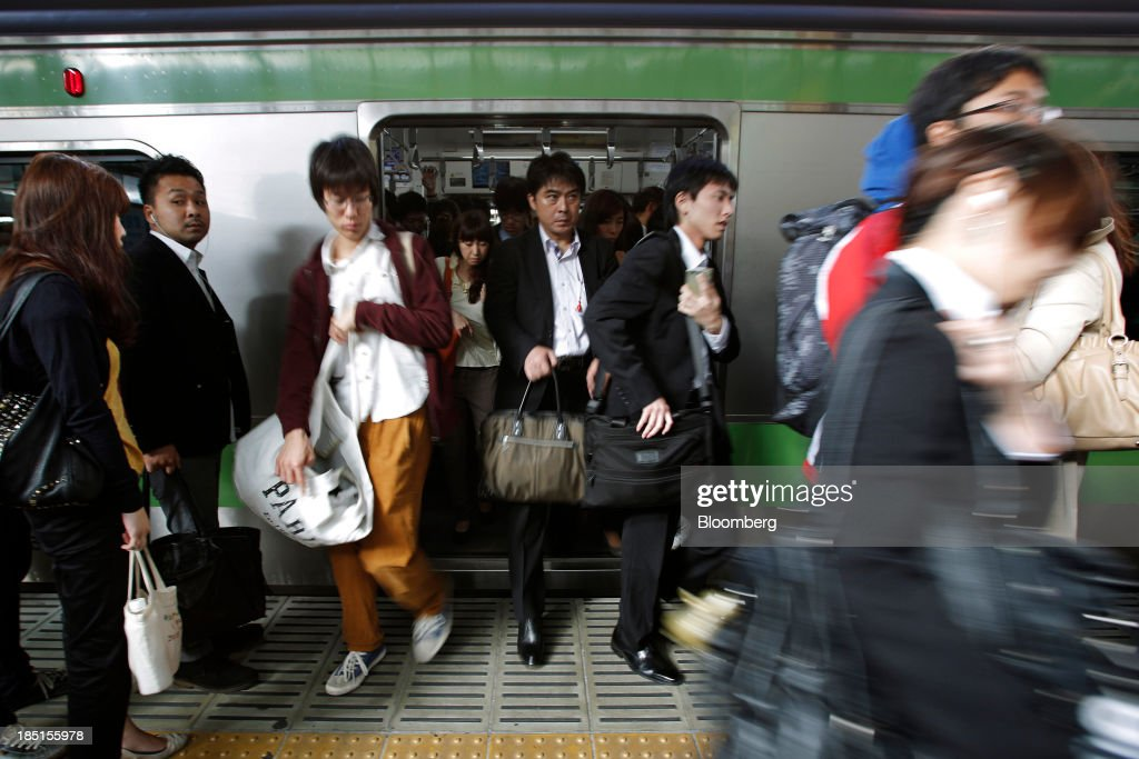 Commuters disembark a train at a station in Tokyo, Japan, on Thursday, Oct. 17, 2013. Asian stocks rose, sending the benchmark index to a five-month high, while the regions bond risk fell and emerging-market currencies strengthened after U.S. lawmakers voted to raise the nations debt limit. Photographer: Kiyoshi Ota/Bloomberg via Getty Images