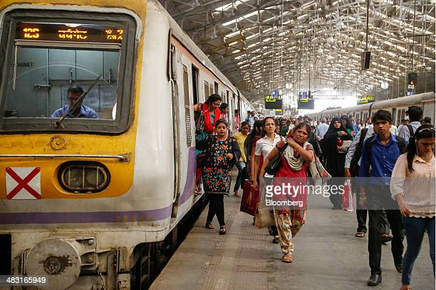 Commuters disembark from a train as others walk along a platform during the morning rush hour at Churchgate Station near the financial district of...