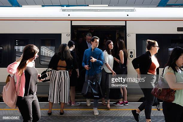 Commuters disembark from a train operated by GoAhead Group Plc's SouthEastern railway franchise after it arrived on a newly opened platform at London...