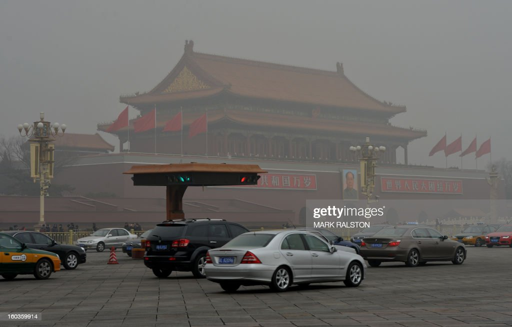 Commuters drive in front of Tiananmen Gate (back) during heavy air pollution in Beijing on January 30, 2013. Beijing urged residents to stay indoors on January 30 as emergency measures were rolled out aimed at countering a heavy cloud of smog blanketing the Chinese capital and swathes of the country. AFP PHOTO/Mark RALSTON