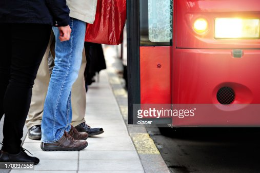 Commuters entering red bus