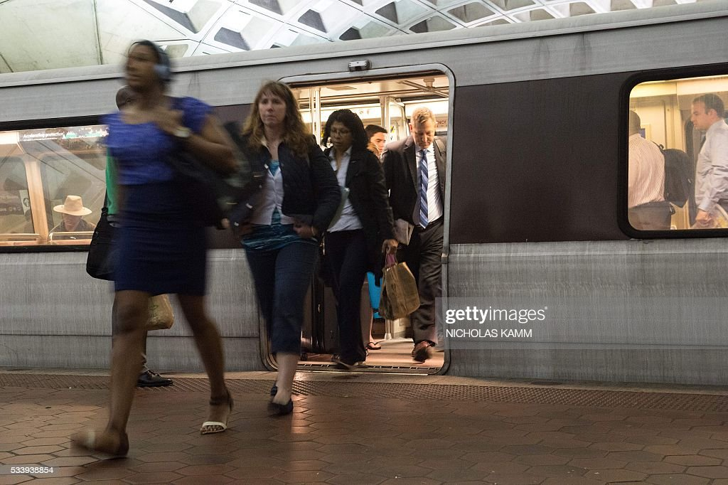 Commuters get off a Metro train as others wait to go aboard at the L'Enfant Plaza station in Washington, DC, on May 24, 2016. Paul Wiedefeld, who used to run the Baltimore-Washington international airport, took over as Metrorail's new general manager in November, assuming what was probably the least wanted job in the city at a really tense time. Wiedefeld has since presented a long-term maintenance plan to improve the system. / AFP / Nicholas Kamm