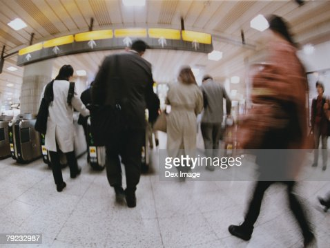 Commuters going though turnstile (blurred motion) : Stock Photo