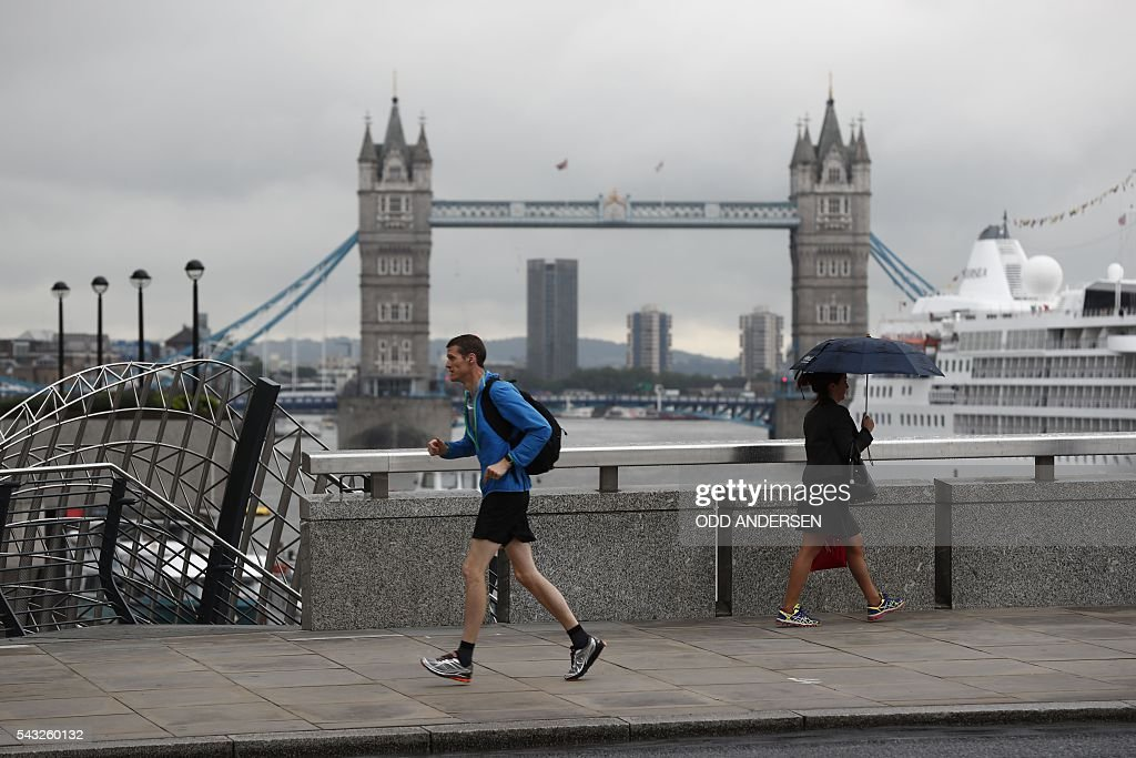 Commuters heading into the City of London walk across London Bridge, in front of Tower Bridge, in central London on June 27, 2016. British Prime Minister David Cameron will gather his cabinet Monday at the start of a crunch week for Europe's leaders after the country's shock vote to leave the EU, seeking to head off further turmoil. / AFP / ODD