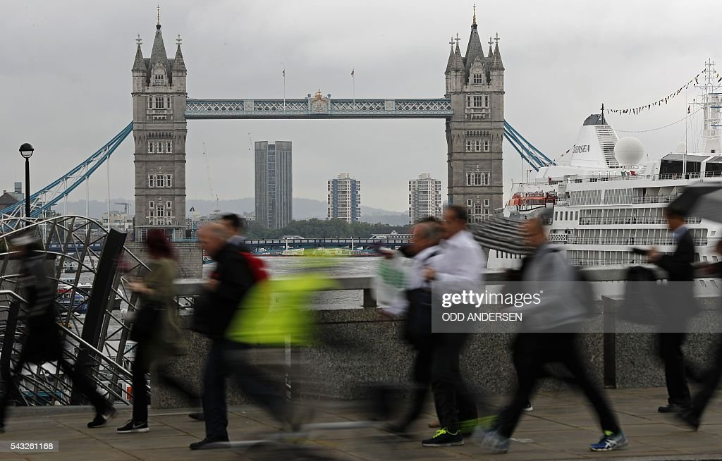Commuters heading into the City of London walk across London Bridge, in front of Tower Bridge, in central London on June 27, 2016. Britain should only trigger Article 50 to leave the EU when it has a 'clear view' of how its future in the bloc looks, finance minister George Osborne said Monday following last week's shock referendum. / AFP / ODD