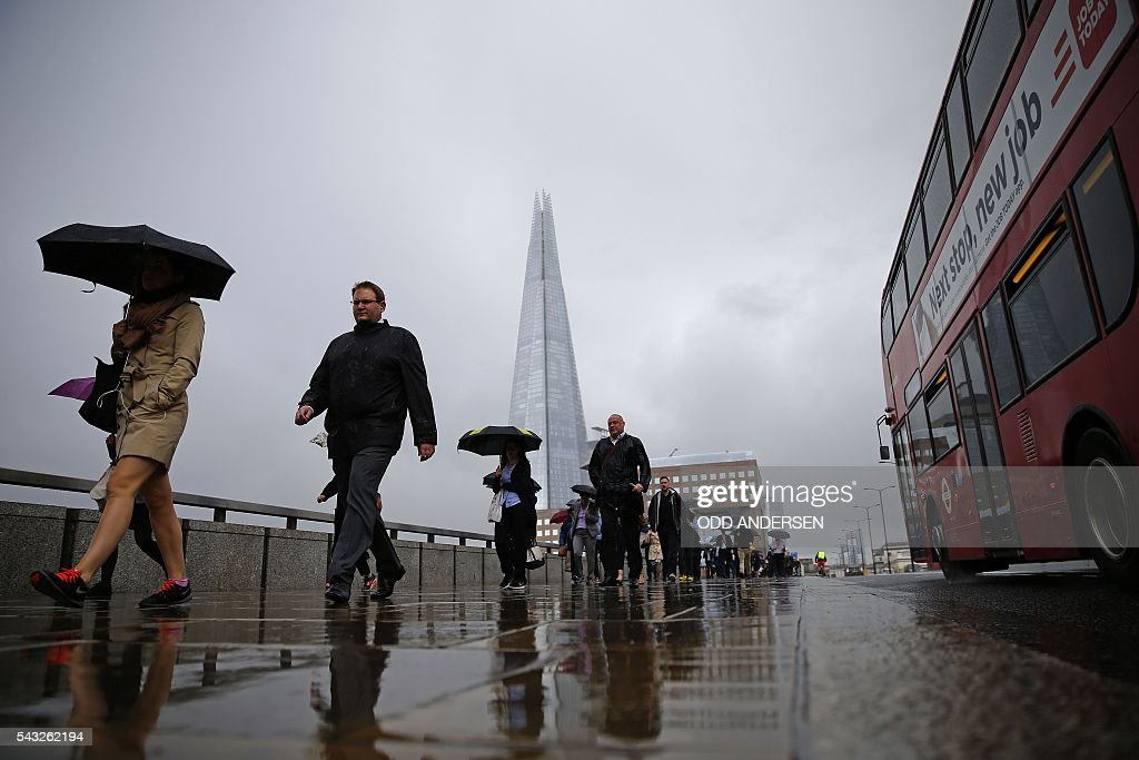 Commuters heading into the City of London walk in the rain across London Bridge, in front of the Shard skyscraper, in central London on June 27, 2016. Britain should only trigger Article 50 to leave the EU when it has a 'clear view' of how its future in the bloc looks, finance minister George Osborne said Monday following last week's shock referendum. / AFP / ODD