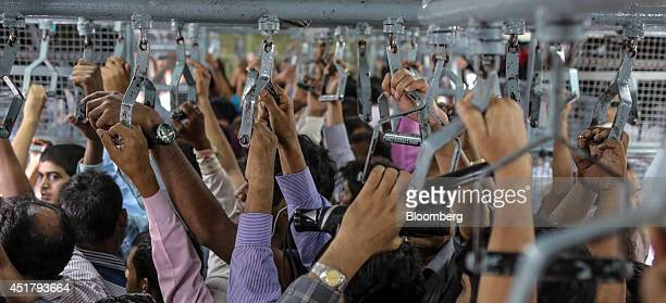Commuters hold on to handles while waiting to disembark from a train as it arrives at Masjid Bundar railway station in Mumbai India on Friday July 4...