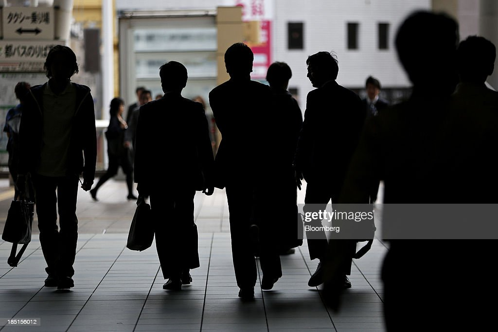 Commuters holding bags are silhouetted as they walk along a street in Tokyo, Japan, on Thursday, Oct. 17, 2013. Asian stocks rose, sending the benchmark index to a five-month high, while the regions bond risk fell and emerging-market currencies strengthened after U.S. lawmakers voted to raise the nations debt limit. Photographer: Kiyoshi Ota/Bloomberg via Getty Images