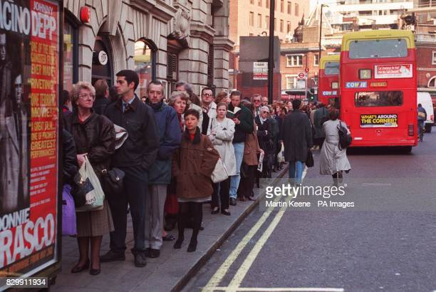 Commuters in London wait in a queue for Buses outside Victoria station after a series of security alerts caused the evacuation of mainline and...