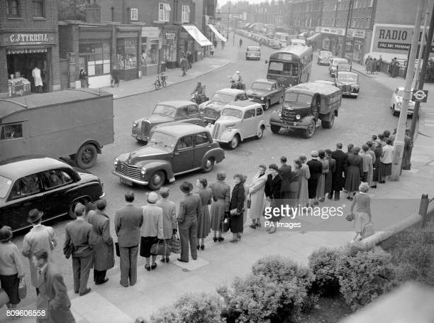 Commuters in Norbury Surrey queue for a bus as a long line of vehicles drive towards London on the first day of the rail strike Many of the cars were...
