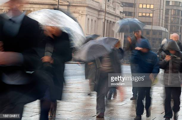 Commuters in the rain with umbrellas with movement blur