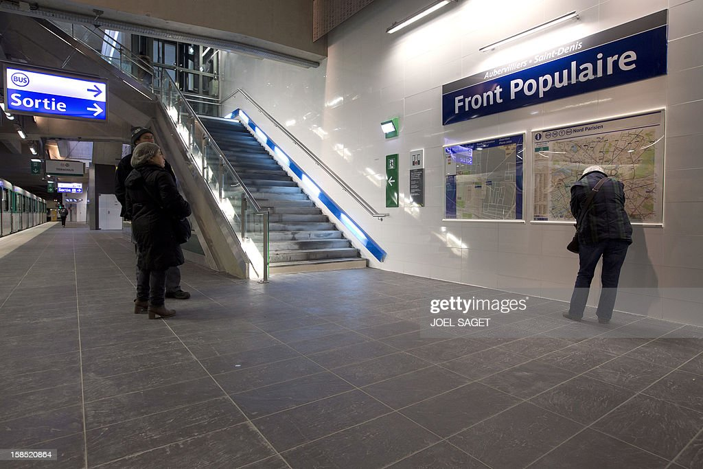 Commuters look at information boards at the Front Populaire subway station on its inauguration day on December 18, 2012 in Aubervilliers-Saint-Denis, north of Paris.