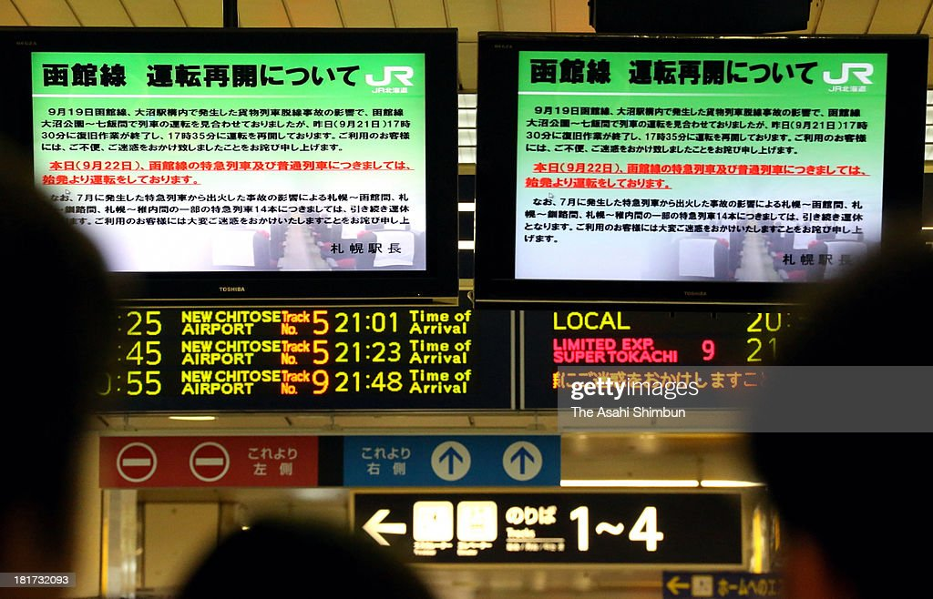Commuters look up the monitor displaying the service suspension due to the derailment at JR Hokkaido Sapporo station on September 22, 2013 in Sapporo, Hokkaido, Japan. JR Hokkaido, long known for its poor safety record, said it found wider-than-standard gauges and other irregular rail conditions left unrectified at 97 locations, after one such case may have resulted in the derailment of a cargo train on September 19.