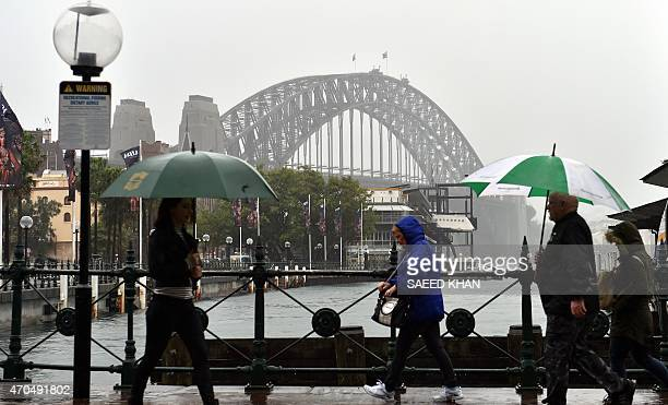 Commuters make their way in the heavy rain in front of the Sydney iconic Habour Bridge on April 21 2015 Australia's biggest city Sydney and...
