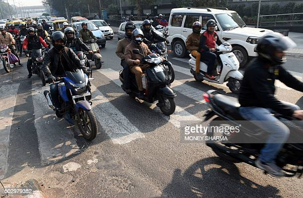 Commuters on motorbikes are seen at a traffic intersection in New Delhi on December 31 2015 Millions of Delhi residents will have to find alternative...