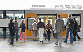 'Commuters on platform boarding train, rear view (blurred motion)'