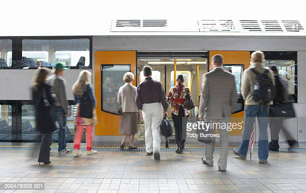 'Commuters on platform boarding train, rear view (blurred motion)'