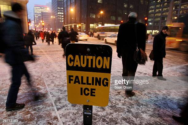 Commuters pass a caution sign outside the Sear's Tower amid frigid temperatures and snow after leaving work in the Loop February 11 2008 in Chicago...