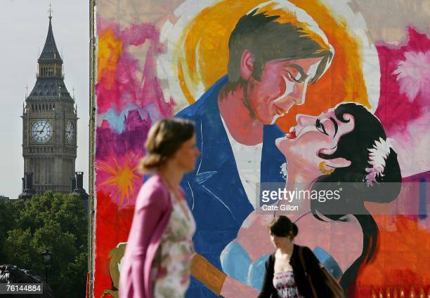 Commuters pass a giant painting of a Bollywood film poster in Trafalgar Square before heading to work on August 17 2007 in London England The...