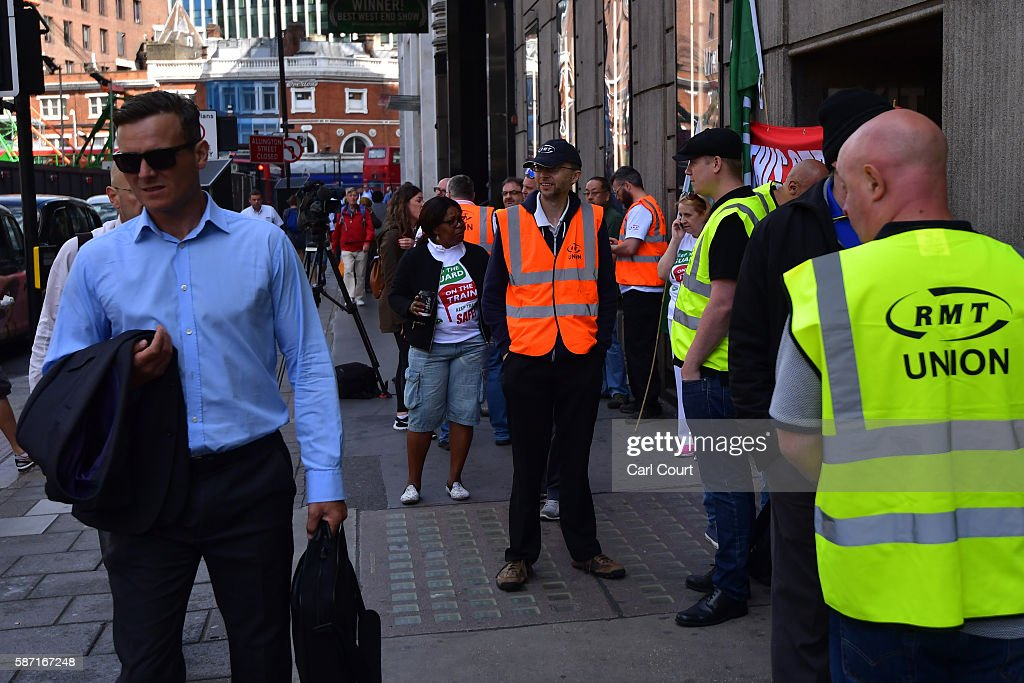 Commuters pass as union members man a picket line at Victoria station on August 8 2016 in London England Hundreds of thousands of Southern rail...