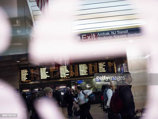 Commuters pass in front of a departure board at the Long Island Railroad Co concourse inside Pennsylvania Station in New York US on Friday May 26...