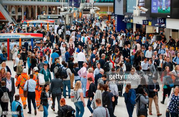 Commuters pass the platforms as they walk through London Waterloo rail station in central London on August 7 as Network Rail commences major work to...