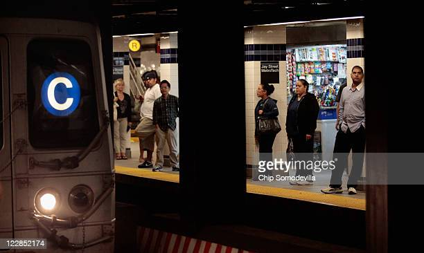 Commuters prepare to board the C train at the Jay Street subway station August 29 2011 in the Brooklyn borough of New York City One day after...