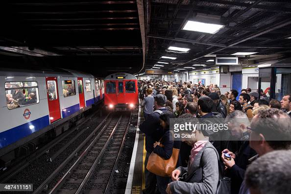 Commuters prepare to travel on the District Line of the London Underground which is running a limited service due to industrial action on April 30...